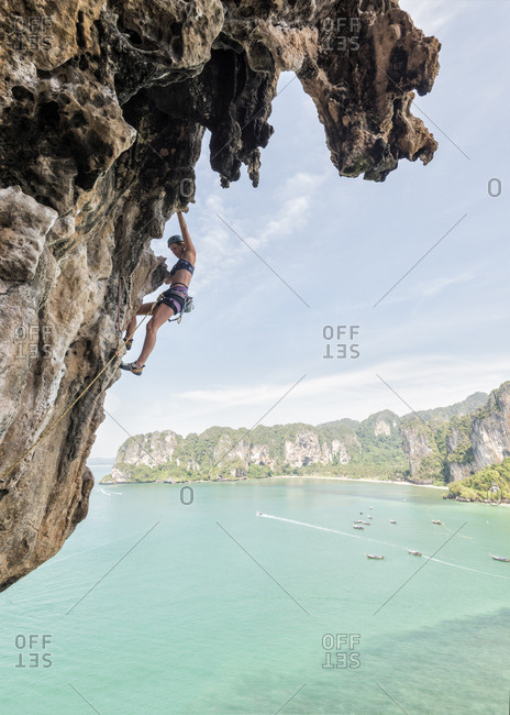 Thailand- Krabi- Thaiwand wall- woman climbing in rock wall above the sea