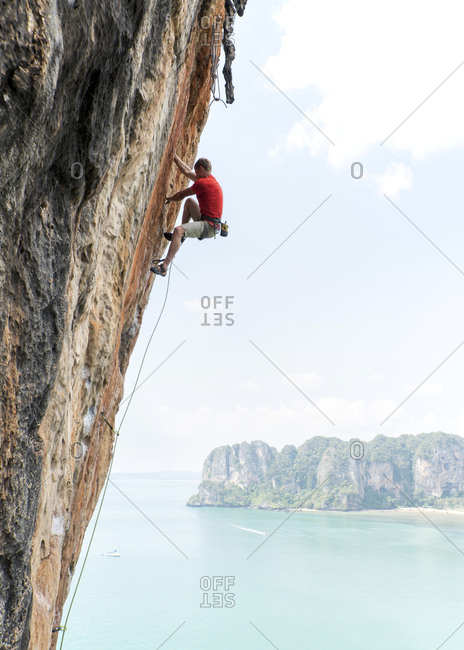 Thailand- Krabi- Thaiwand wall- man climbing in rock wall above the sea