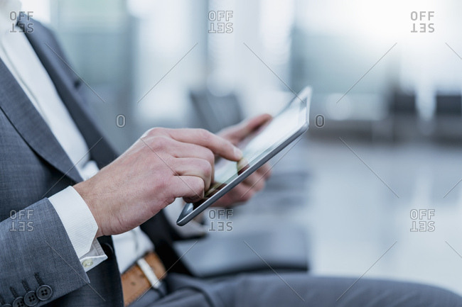 Close-upof businessman sitting in waiting area using tablet