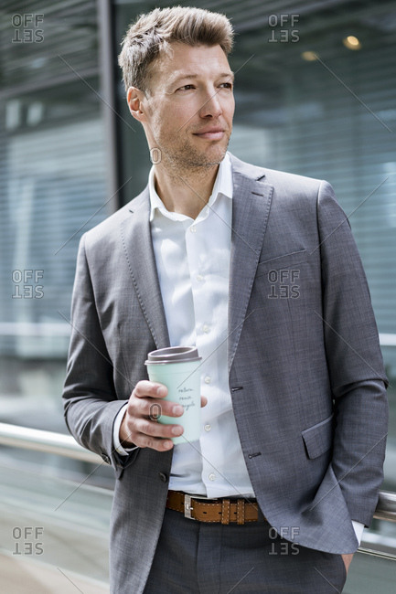 Businessman with takeaway coffee outside in the city