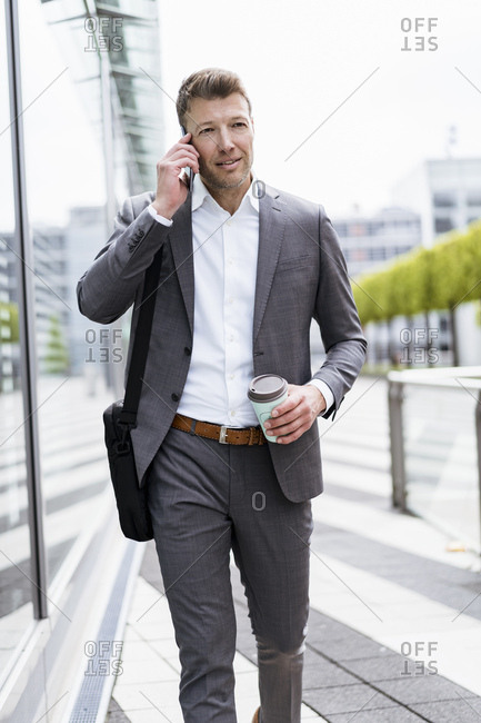 Businessman on cell phone on the move in the city