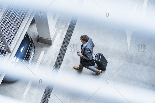 Top view of businessman walking with baggage and takeaway coffee at a car park