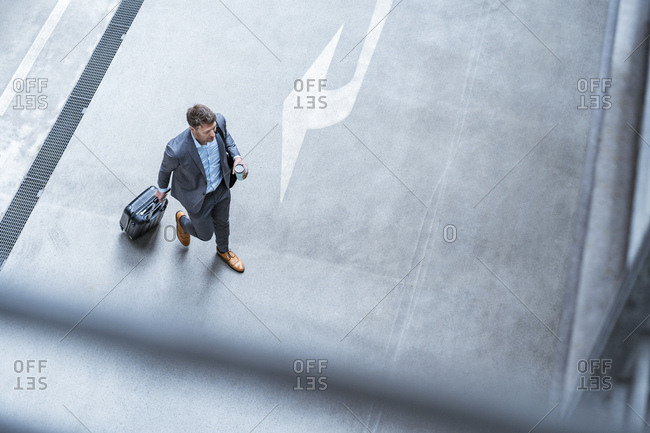 Top view of businessman walking with baggage and takeaway coffee