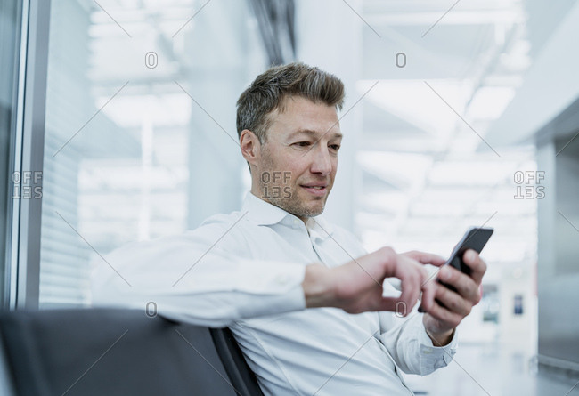 Businessman sitting in waiting area using cell phone