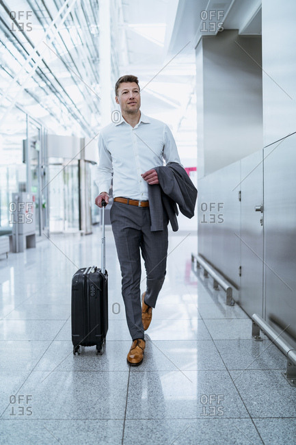 Businessman walking with baggage at the airport