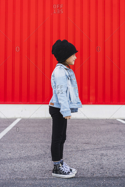 Fashionable little girl wearing denim jacket- black cap and sneakers