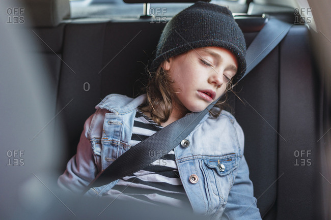 Portrait of sleeping little girl on back seat of a car