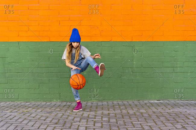 Young girl playing basketball- dribbling and lifting leg