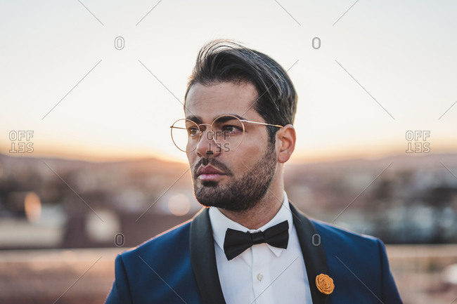 Portrait of stylish man on roof terrace at sunset