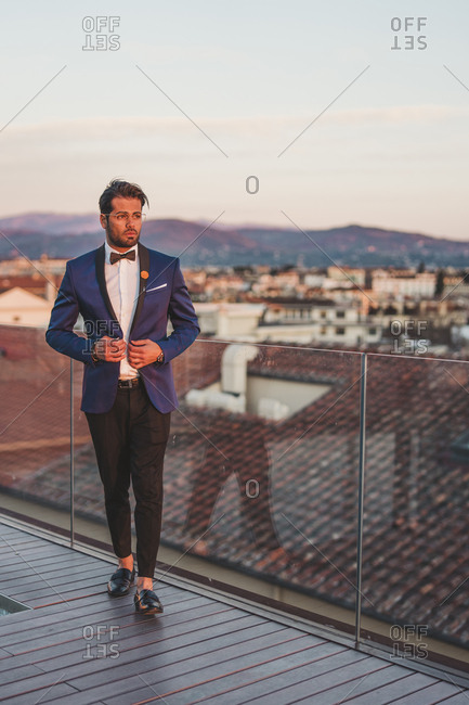 Italy- Florence- Portrait of stylish man on roof terrace at sunset
