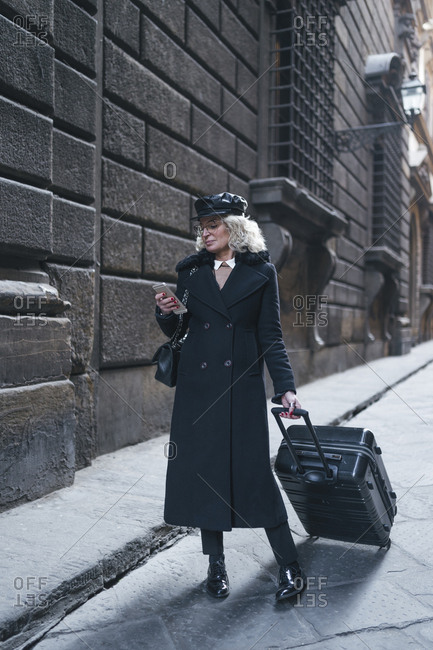 Mature businesswoman wearing black coat and leather cap on business trip looking at mobile phone