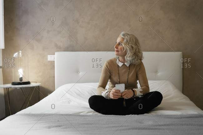 Mature businesswoman sitting on bed with mobile phone looking out of window