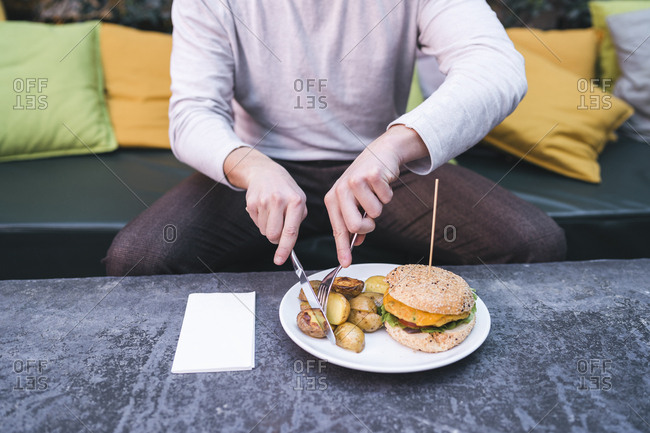 Young man sitting on couch in a restaurant having a vegan burger with potatoes for lunch
