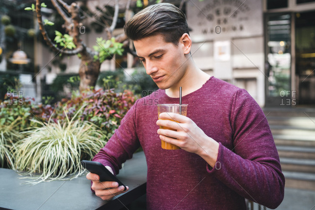 Young man having a drink and using cell phone