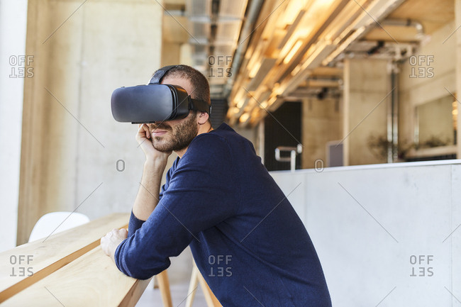 Young man wearing VR glasses in modern office