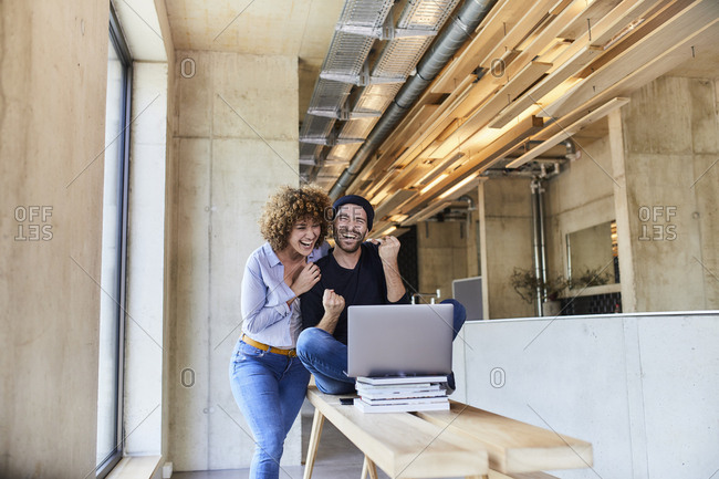 Excited man and woman with laptop in modern office