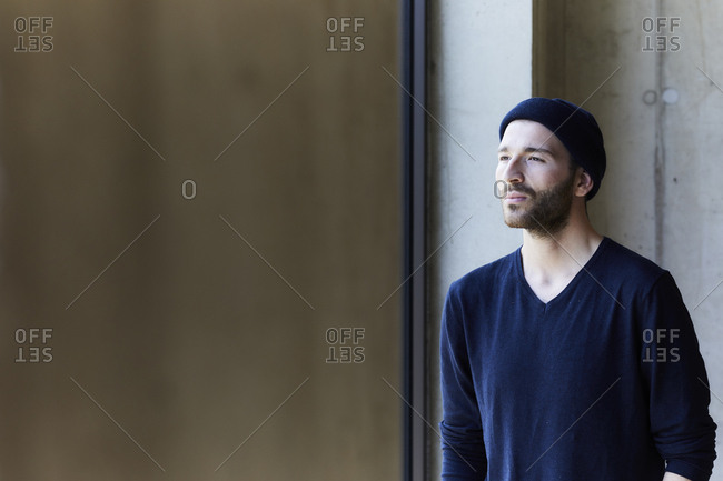 Young man wearing beanie looking out of window