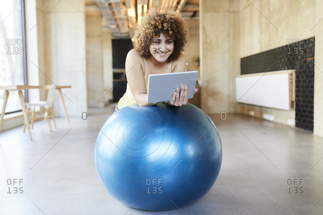 Smiling woman using tablet on fitness ball in modern office
