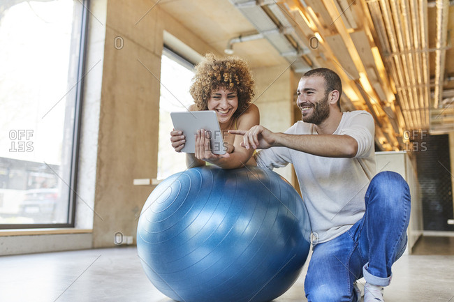 Happy man and woman using tablet on fitness ball in modern office