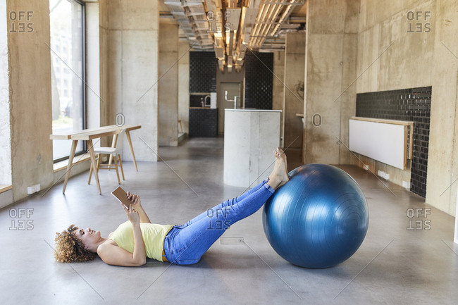 Woman with fitness ball lying on the floor using tablet in modern office