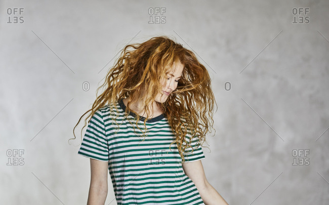 Portrait of redheaded young woman wearing striped t-shirt dancing