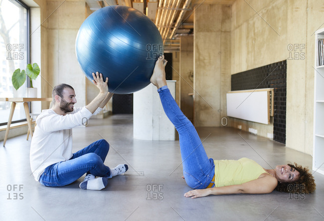 Happy man and woman practicing with fitness ball in modern office