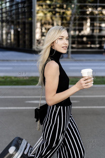 Portrait of smiling blond woman with coffee to go and wheeled luggage