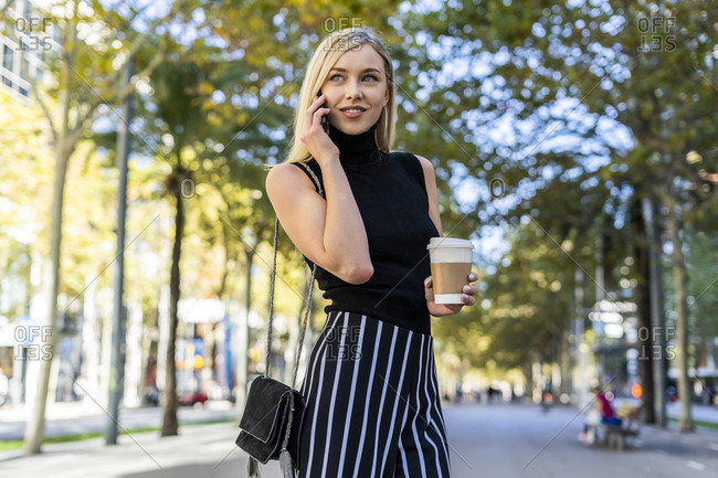 Portrait of smiling blond woman with coffee to go on the phone