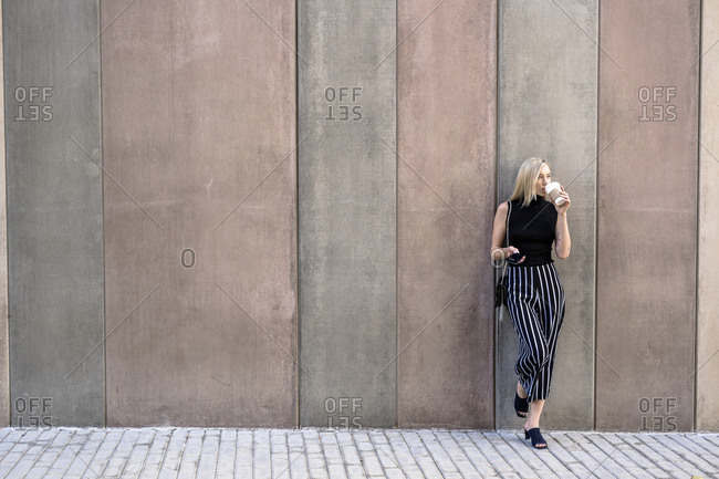 Young blond woman with cell phone leaning against wall drinking coffee to go