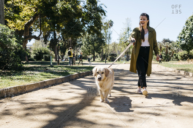 Happy woman going walkies in city park with her Labrador Retriever