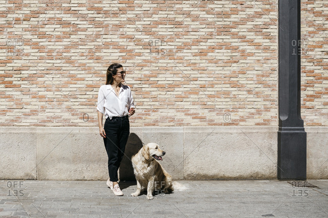 Woman and her Labrador Retriever waiting in front of patterned brick wall looking at distance
