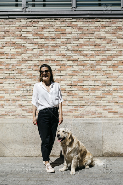Laughing woman standing besides her Labrador Retriever in front of patterned brick wall