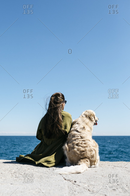 Back view of woman sitting besides her Labrador Retriever at quay looking to the sea