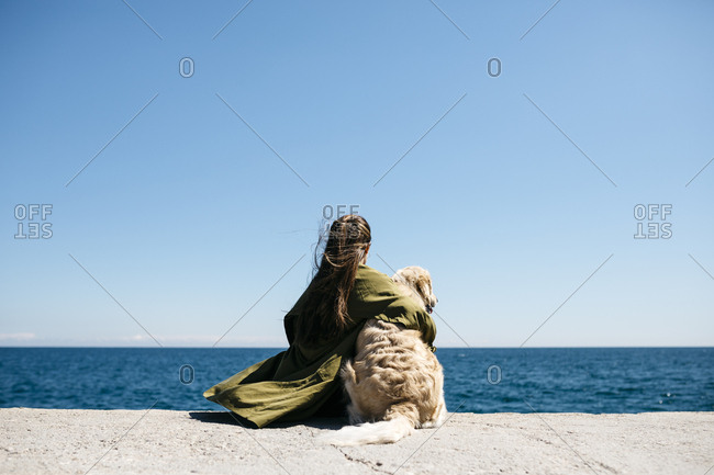 Back view of woman sitting besides her Labrador Retriever at quay looking at horizon