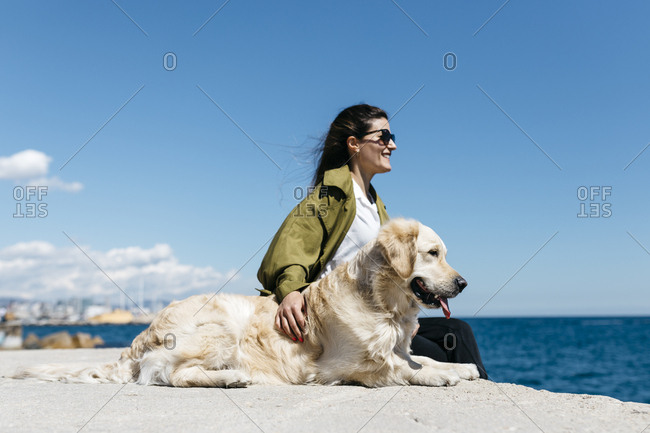Happy woman sitting besides her Labrador Retriever at quay looking to the sea