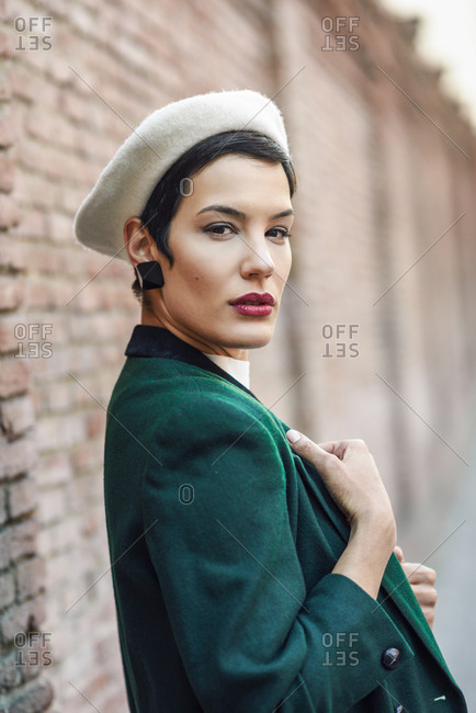 Portrait of fashionable young woman at a brick wall