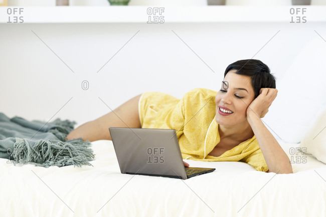 Smiling young woman lying in bed using laptop