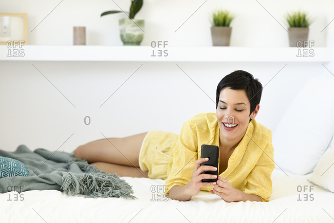 Smiling young woman using cell phone in bed