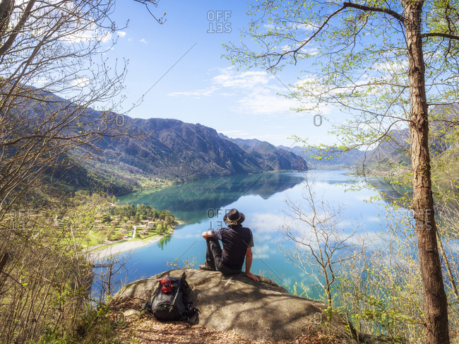 Italy- Lombardy- spring at Lake Idro- hiker sitting on observation point