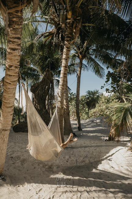 Mexico- Quintana Roo- Tulum- young woman lying in hammock on the beach