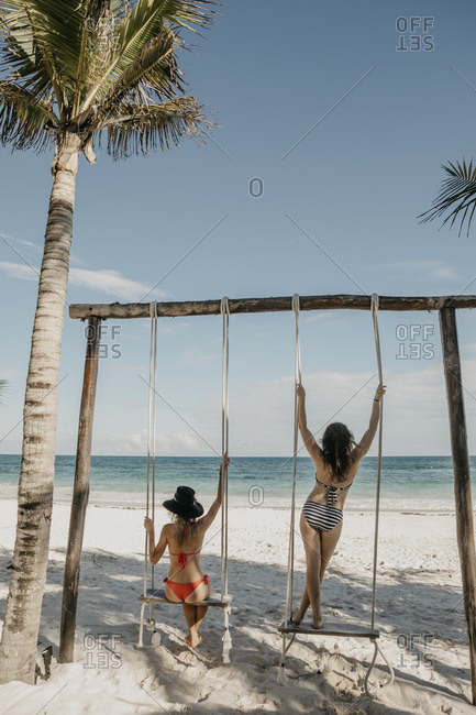 Mexico- Quintana Roo- Tulum- two young women on a swing on the beach
