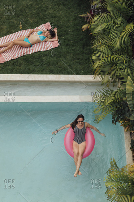 Two young women relaxing at swimming pool