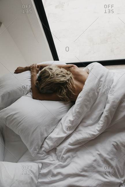 Blond young woman lying in bed