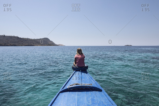 Indonesia- Komodo National Park- girl sitting on bow of a boat
