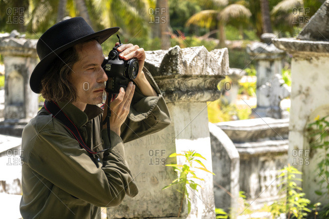 Seychelles- La Digue- man photographing gravestones at old grave yard