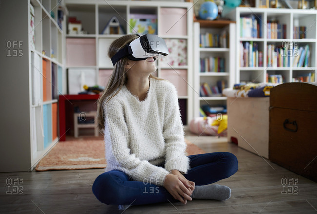 Girl sitting in her room- using VR goggles
