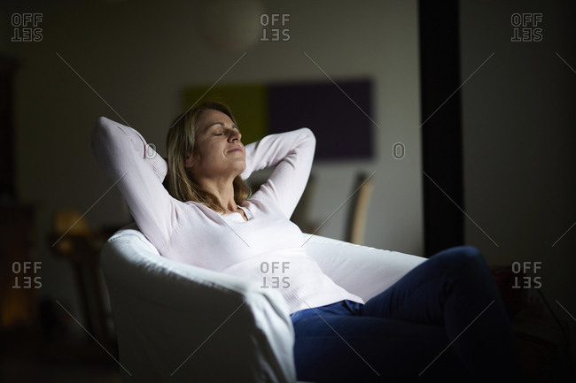 Woman sitting at home- relaxing in arm chair