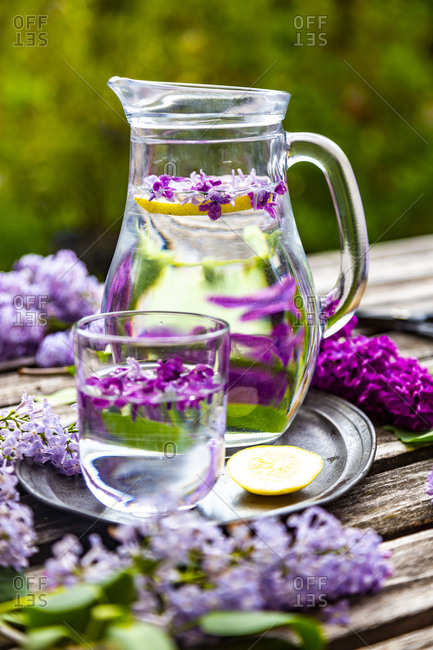 Jar with glass of water with lilac syrup and lemon