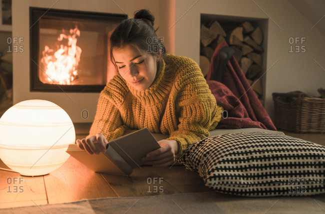 Young woman reading book at the fireplace at home