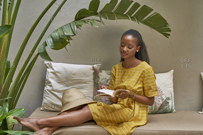 Relaxed young woman sitting on a couch reading a book